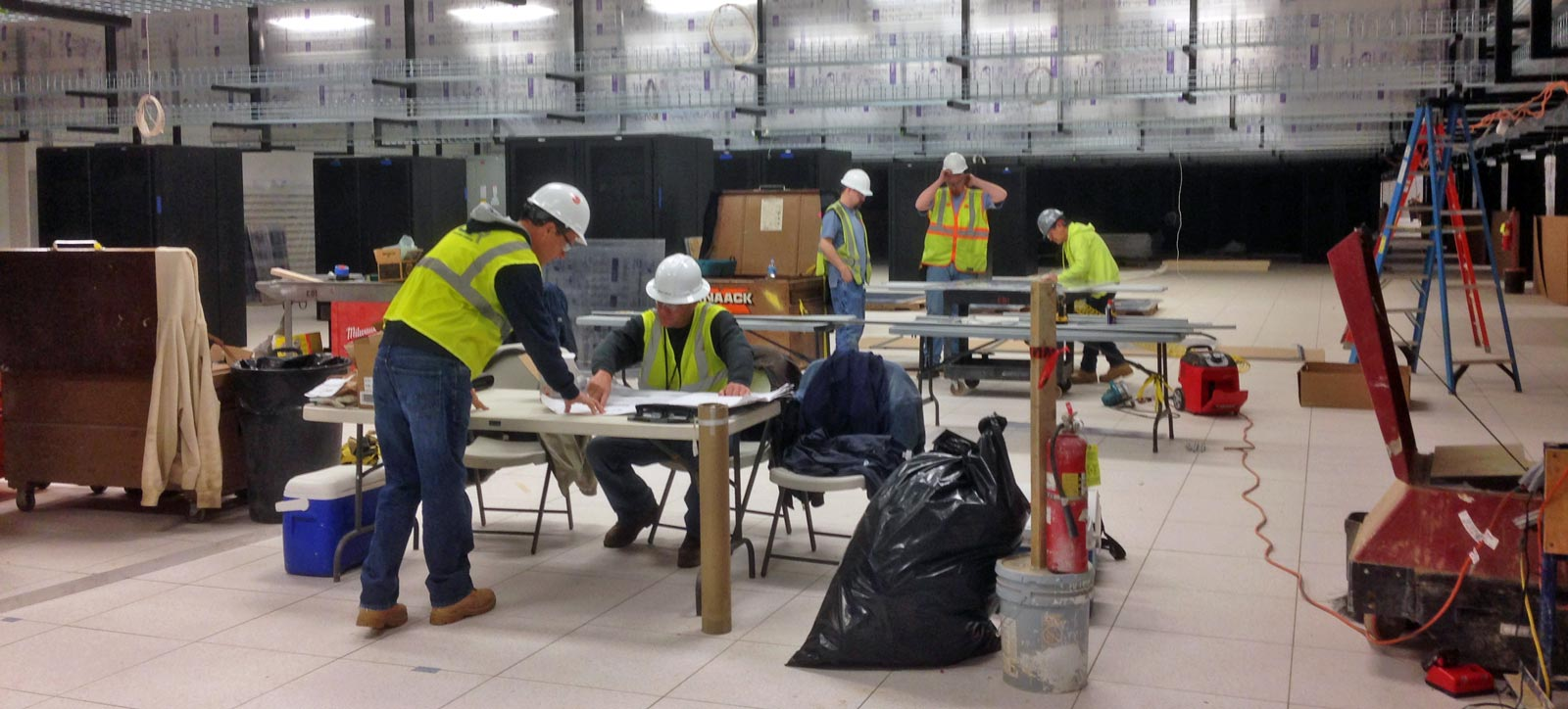 workers installing aisle containment system in data center