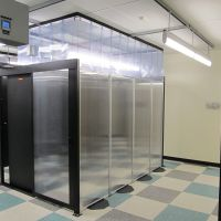 Aisle containment panel wall in data center with sliding single door