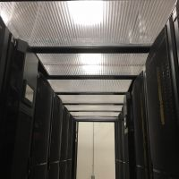 Looking down aisle containment server row with lights and thermal drop away panels.